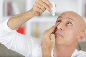 man using eye drops for dry eyes